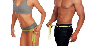 Bodies of man and woman measuring the waist with tape measure. Bodies of men and women measuring the waist with tape isolated on a white background Royalty Free Stock Images