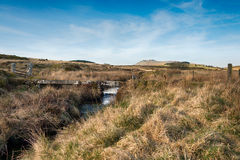 Bodmin Moor. A small stone clapper bridge over De Lank River on Bodmin moor in Cornwall as it winds it's way past Broown Willy, with Roughtor in the far distance Stock Image