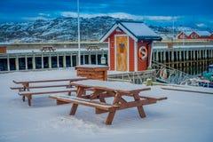 Bodo, Norvège - 9 avril 2018 : Vue extérieure de table en bois dehors à couvrir de neige dans le secteur de port de marina dedans images stock