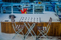 Bodo, Norway - April 09, 2018: Outdoor view of mixed mettalic and wooden chair at outdoors covered with snow in the. Marina port area in Bodo, Norway Stock Photo