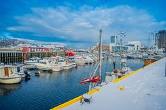 Bodo, Norway - April 09, 2018: Outdoor view of the shore and marina area with some boats in a row in the water located. In the port of Bodo, in Norway Royalty Free Stock Images