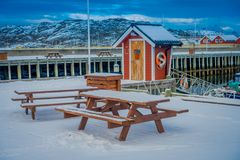 Bodo, Norway - April 09, 2018: Outdoor view of wooden table at outdoors covered with snow in the marina port area in. Bodo, Norway Stock Images