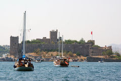 Bodrum beach with ancient citadel and boats Stock Images