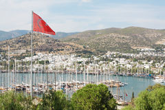 Bodrum and Turkish flag, Turkey. View of Bodrum harbour and marina from St Peter's castle, in Mugla Province, Turkey. The Turkish flag is on the foreground and royalty free stock images