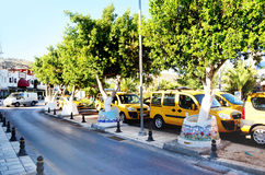 Bodrum, Turquía 2014 calle con los árboles verdes y los taxis amarillos Imágenes de archivo libres de regalías