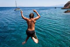 BODRUM, TURQUÍA - 23 DE JULIO: Muchacho no identificado que salta en el mar de Fotografía de archivo