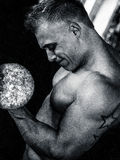 Bodybuilder training biceps. With dumbbell in gym. Monochrome stock photography