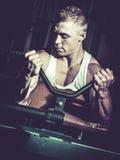 Bodybuilder training biceps. In gym stock photography