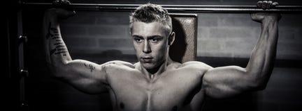 Bodybuilder training weights. Bodybuilder training with machine in gym. Monochrome stock photo