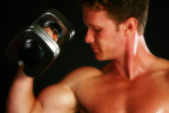 Body. Attractive thirty something man lifting weights over black stock photo