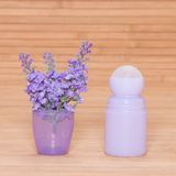 Body antiperspirant deodorant roll-on with flowers in the cap Royalty Free Stock Photography