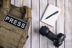 Body armor for journalist, notebook and camera. Body armor for journalist with patch `press`, notebook with pen and camera on wooden table. Top view Stock Photo