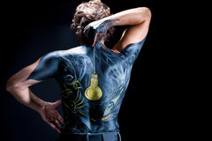 Body art on man. Man body art/body-art with bright pixture on the back made with acrylic paint isolated on black background Stock Photography