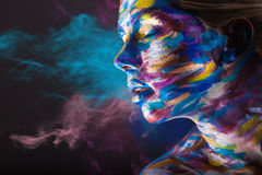 Body art. Young woman with colorful make-up and body art on a black background with multi-colored smoke Stock Image