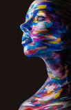 Body art. Young woman with colorful makeup and body art on a black background Royalty Free Stock Image