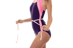 The body of an attractive young girl in a body that measures out a waist measuring tape is isolated on a white Stock Photography