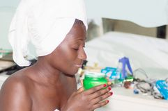 Body beauty. This young woman is very happy with the perfume of her ointment Stock Photo