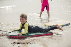 Body Boarding at the Beach. Little boy having fun at the beach, being pulled along on a body board Stock Images