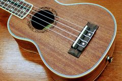 Body of brown color wood ukulele. on the real wood table background Royalty Free Stock Photos