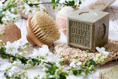 Body brush and olive oil soap for natural washing up. Cleansing concept - beautiful body brush and organic olive oil solid soap with beige pebbles in fresh white Royalty Free Stock Images