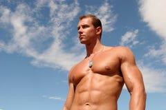 Body builder. Muscular body builder man against blue sky Stock Image