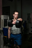 Body builder doing heavy weight exercise for shoulder white dumbbell Stock Image