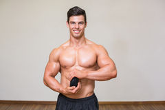 Body builder holding bottle with supplements in gym Stock Images