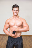Body builder holding bottle with supplements in gym Royalty Free Stock Image
