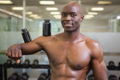 Body builder holding bottles with supplements on biceps Royalty Free Stock Photography