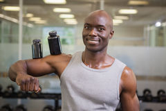 Body builder holding bottles with supplements on biceps Stock Images