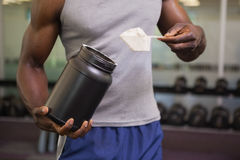 Body builder holding a scoop of protein mix in gym Stock Photos