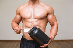 Body builder holding a scoop of protein mix in gym. Mid section of a body builder holding a scoop of protein mix in gym Royalty Free Stock Image