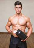 Body builder holding a scoop of protein mix in gym Stock Images