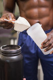 Body builder holding a scoop of protein mix Royalty Free Stock Image