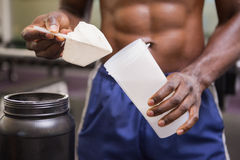 Body builder holding a scoop of protein mix Royalty Free Stock Photography