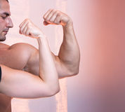 Body builder portrait with biceps muscle i. Solated on pink background stock photo
