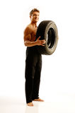 Body-building. A man with a car tire Royalty Free Stock Photos