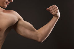Body-building. A young man shows his muscles on his arm Royalty Free Stock Photos