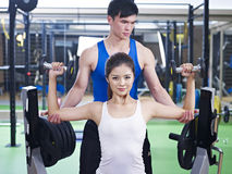 Body building exercise. Young women doing body building exercise with help from trainer Stock Photo