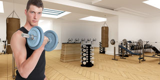 Body building. Young man in a gym lifting a dumbbell Stock Images