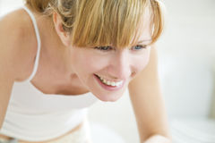 Body care. Beautiful young woman looking herself in the mirror and smiling royalty free stock images