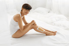 Body Care. Beautiful Woman Removing Hair With Wax From Long Legs Royalty Free Stock Photos