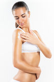 Body care. Beautiful young woman applying body lotion Royalty Free Stock Photography