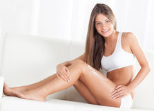Body care. Beautiful young woman applying body lotion. Looking at camera Stock Photos