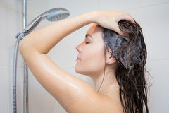 Body care concept - young woman washing her hair with shampoo in Stock Photo