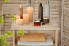 Body care cosmetics and burning candles. On table Stock Image
