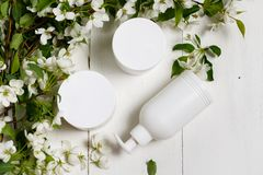Body care cosmetics white bottle with flowers flat lay royalty free stock photo