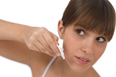 Body care - Female teenager cleaning face. With cotton pad, removing make-up Royalty Free Stock Images