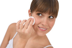 Body care - Female teenager cleaning face. With cotton pad, removing make-up Stock Photo