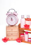 Body care objects and retro alarm clock. A Cabinet with three shelves , alarm clock on top and body care accessories isolated on white background Stock Image